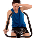 Male teenager wiping brow exhausted after fitness workout on an exercise bike.  White background,