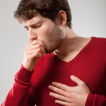 Man with sick lungs holding his chest and coughing