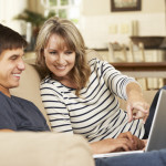 Mother With Teenage Son Sitting On Sofa At Home Using Laptop