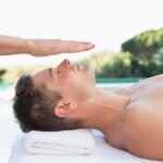 Peaceful man getting reiki treatment poolside