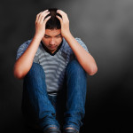 Sad asian teenager boy sitting on the floor