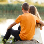 Romantic teen couple talking in the sunset.